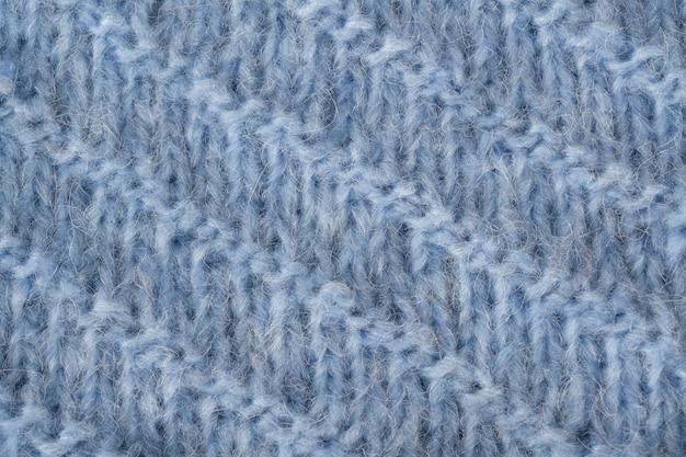 Trama di tessuto soffice maglia blu. maglieria a mano. sfondo dettagliato filato caldo.