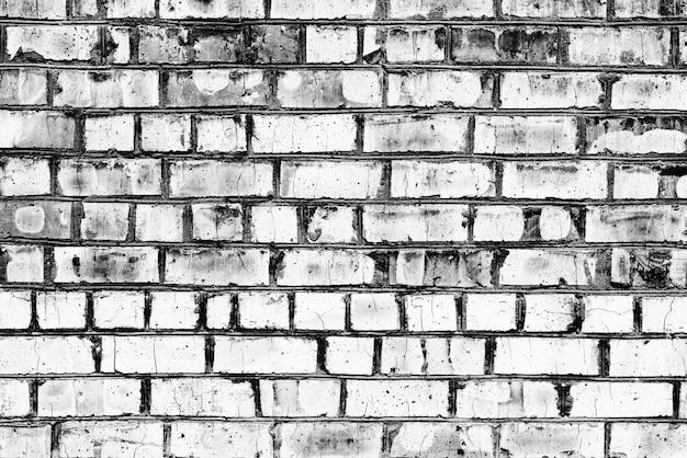 Trama di un muro di mattoni con crepe e graffi che possono essere utilizzati come sfondo