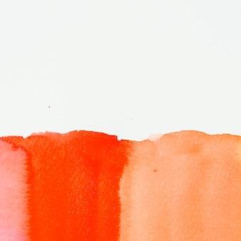 Trama di vernice rossa e arancione su sfondo bianco