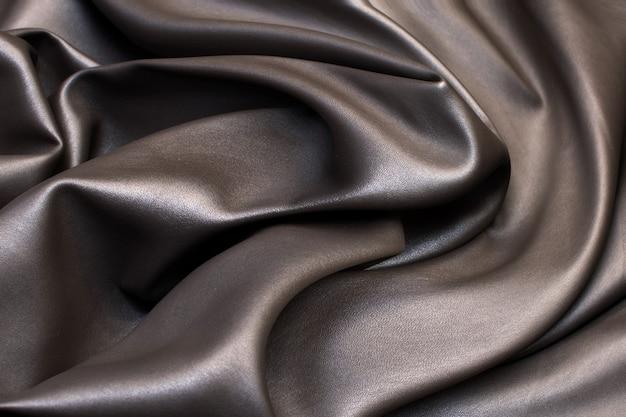 Trama, tessuto sintetico marrone per sartoria. finta pelle.