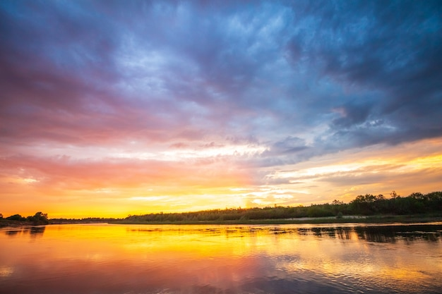 Tramonto ardente sul fiume con la riflessione in acqua