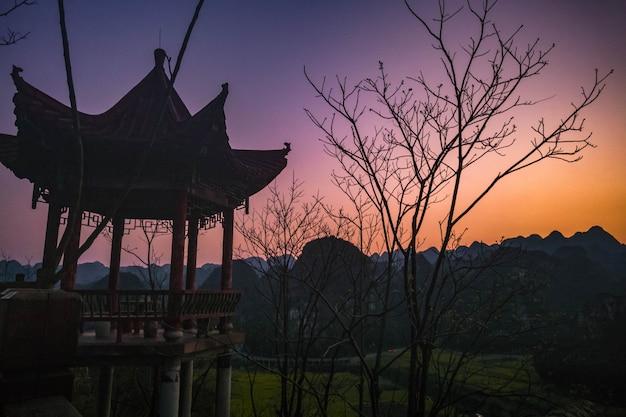 Tramonto con padiglione e campo di fiori di colza al wanfenglin national geological park (foresta delle diecimila cime), cina