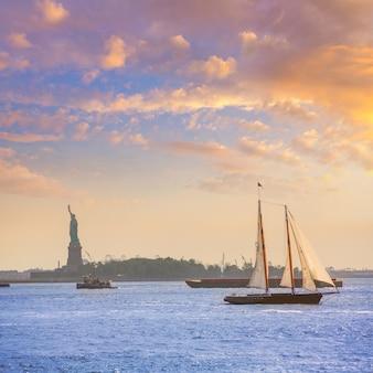 Tramonto della barca a vela di new york e statua della libertà