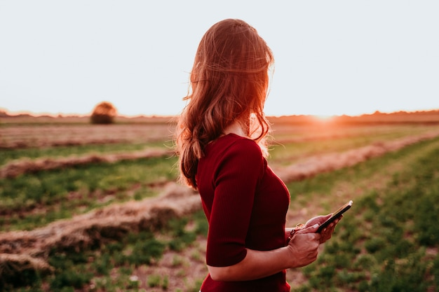 Tramonto di sorveglianza della bella donna caucasica in campagna. utilizzando il telefono cellulare. tecnologia e stile di vita all'aperto