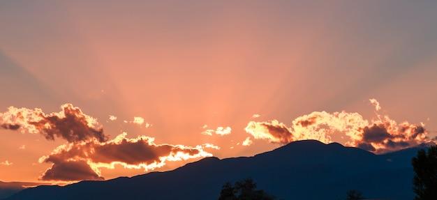 Tramonto in montagna, un bel cielo luminoso con i raggi del sole al tramonto