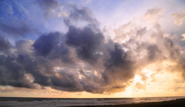 Tramonto in spiaggia con il cielo pieno di nuvole