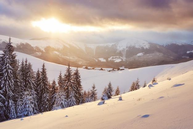 Tramonto maestoso al piccolo villaggio su una collina nevosa sotto l'ucraino