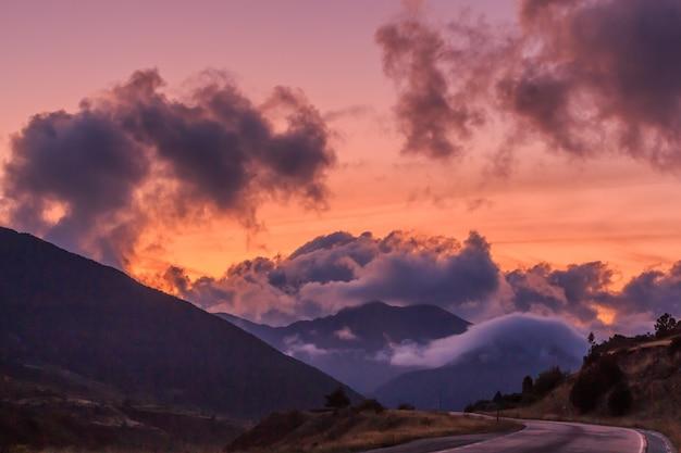 Tramonto rosso in montagna con grandi nuvole bianche.