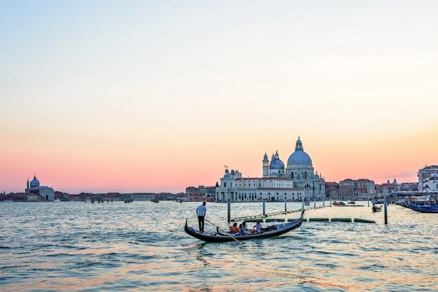 Tramonto rosso vista a una gondola in barca a venezia