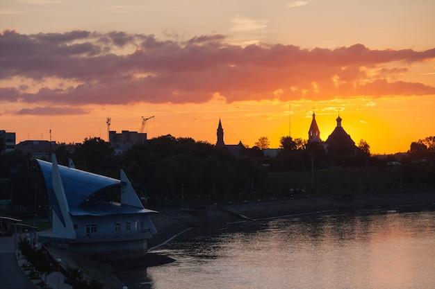 Tramonto sopra la cattedrale e la chiesa, un cielo arancione, nuvole, sole che tramonta all'orizzonte