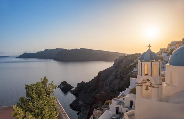 Tramonto sopra la chiesa locale a oia, santorini, grecia