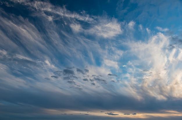 Tramonto su uno sfondo di nuvole bianche in un cielo blu