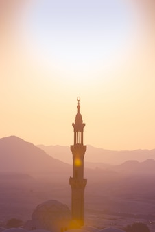 Tramonto sul deserto con moschea musulmana