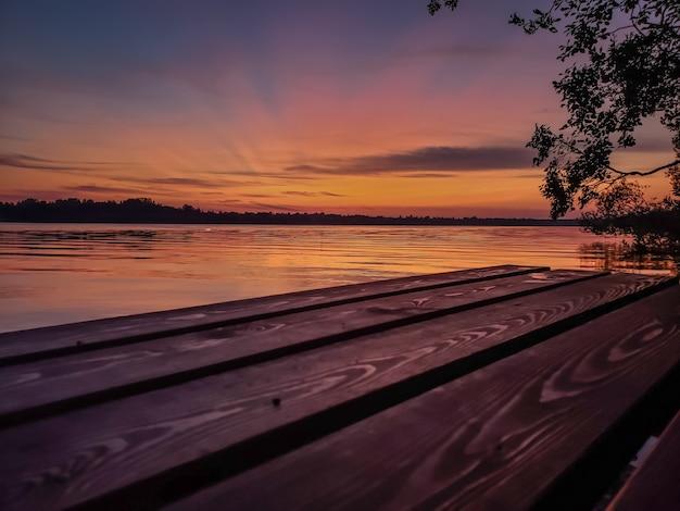 Tramonto sul fiume in estate e molo di legno