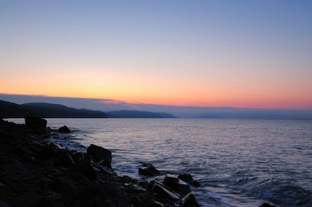 Tramonto sul mare, spiaggia cosparsa di pietre