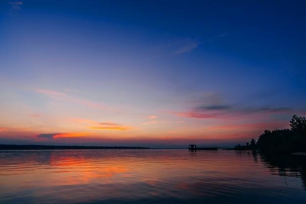 Tramonto sull'acqua del fiume con un molo e una spiaggia con un bel cielo rosso e blu