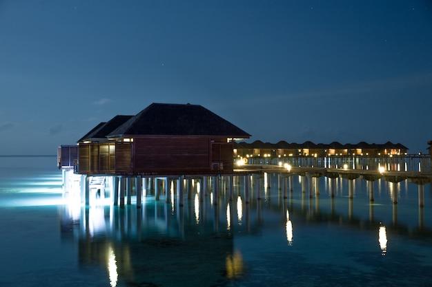 Tramonto sull'isola delle maldive, resort di lusso con ville sull'acqua e molo di legno. bei cielo e nuvole e fondo della spiaggia per la vacanza di vacanze estive e concetto di viaggio