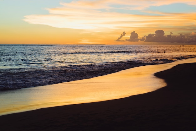 Tramonto sull'oceano. bel cielo luminoso, riflesso nell'acqua, onde.