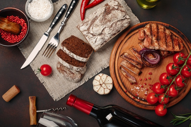 Trancio di maiale alla griglia con bottiglia di vino, bicchiere di vino, cavatappi, coltello, forchetta, pane nero, pomodorini, aglio