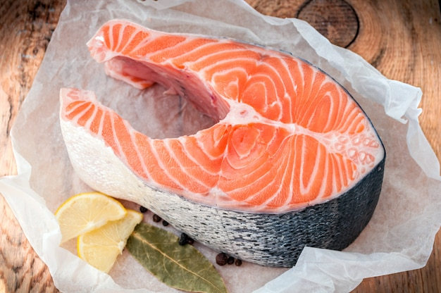 Trancio di pesce di color salmone crudo con il limone e le spezie su rustico di legno