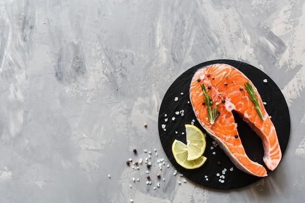 Trancio di pesce di color salmone crudo fresco con le spezie su fondo di pietra scuro