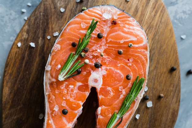 Trancio di pesce di color salmone crudo fresco con le spezie sul bordo di legno