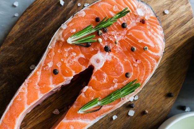 Trancio di pesce di color salmone fresco con le spezie sul primo piano grigio