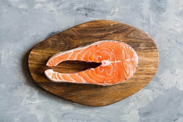 Trancio di pesce di color salmone fresco su fondo grigio