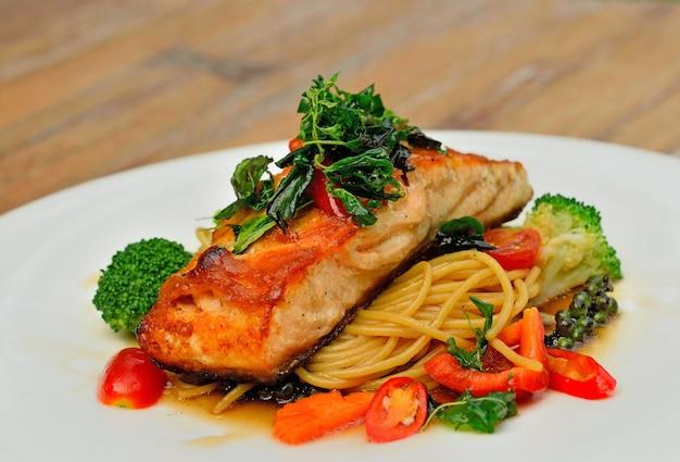 Trancio di salmone al forno con spaghetti sul piatto bianco
