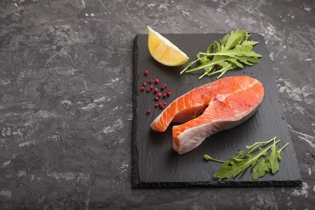 Trancio di salmone con rucola e limone su una tavola di ardesia nera su una superficie di cemento nera. vista laterale, copia spazio.