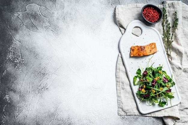 Trancio di salmone con rucola, lattuga e mirtilli rossi. sfondo grigio. vista dall'alto. copia spazio