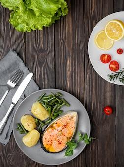 Trancio di salmone cotto con patate e fagiolini su un piatto