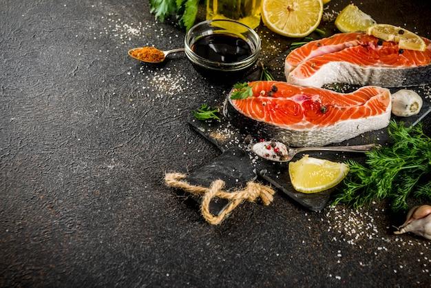 Trancio di salmone crudo con limone, erbe aromatiche, olio d'oliva, pronto per la griglia