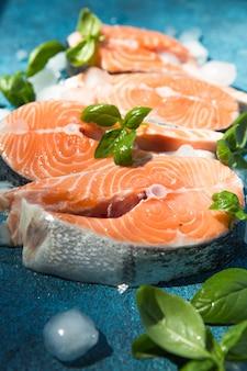 Trancio di salmone crudo e fresco su una tavola di pietra e basilico intorno. pesce rosso salmone crudo.