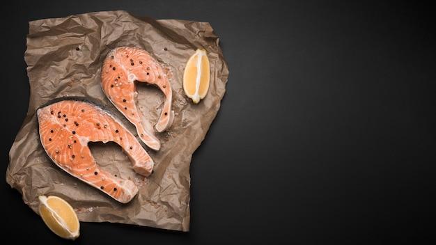 Trancio di salmone crudo piatto e limone con copia-spazio