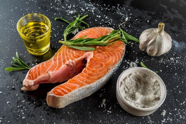 Trancio di salmone di pesce biologico crudo con spezie ed erbe aromatiche