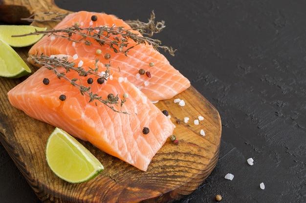 Trancio di salmone pesce crudo preparato per la cottura. vista dall'alto sul tavolo nero.