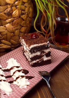 Trancio di tiramisù a base di cioccolato e spugna bianca. un pezzo di dessert su tavole di legno.