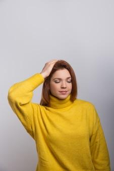 Tranquilla giovane donna con la mano sulla testa