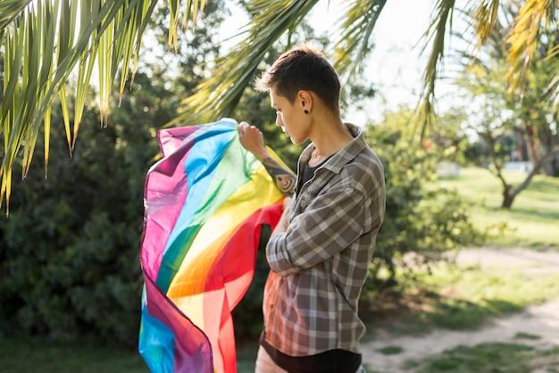 Transgender mantenendo la bandiera lgbt nel parco