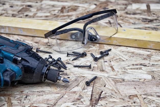 Trapano elettrico con occhiali per la sicurezza degli occhi e livello di costruzione