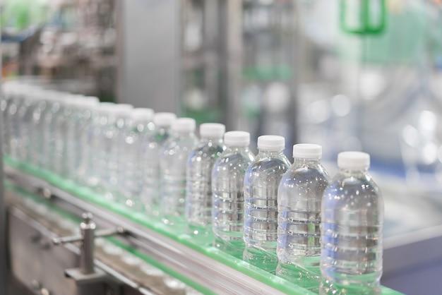 Trasferimento bottiglie d'acqua trasparenti sul sistema di nastri trasportatori.