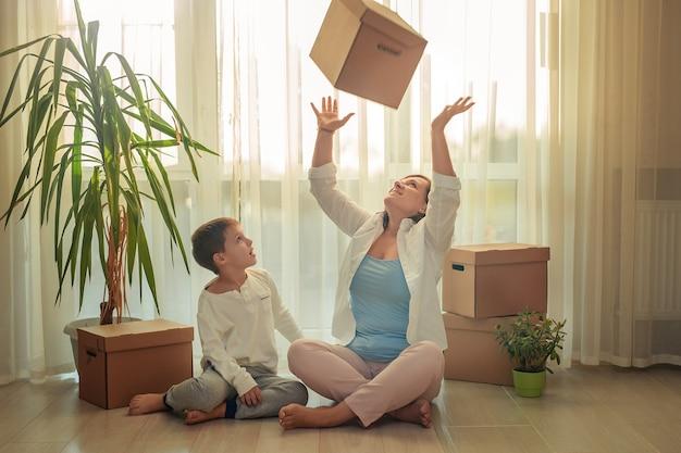 Trasferirsi in una nuova casa. madre felice e figlio che selezionano le scatole