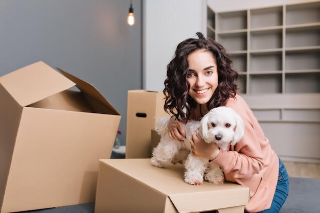 Trasferirsi nel nuovo appartamento di una giovane donna graziosa con un cagnolino. rilassarsi su scatole di cartone intorno al letto con animali domestici, sorridere, esprimere positività