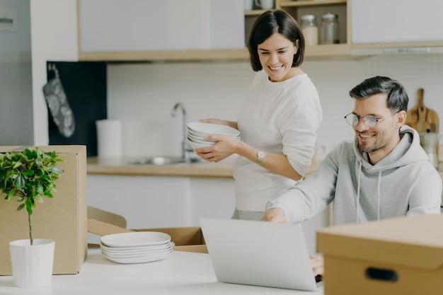 Trasloco e immobili. la donna bruna premurosa tiene una pila di piatti, disimballa oggetti personali, il marito le chiede consigli, sceglie qualcosa da acquistare in internet, focalizzata sul computer portatile