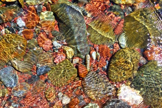 Trasparenza delle rocce rosse del fondo dell'acqua del fiume
