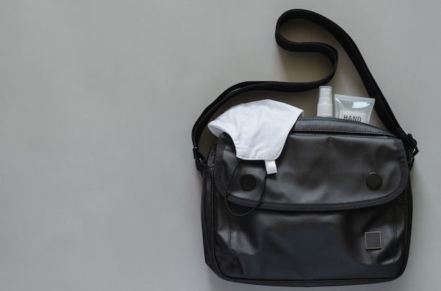 Trasportare la borsa con maschera, spray alcolico e gel disinfettante per le mani per proteggere il coronavirus o il covid-19 quando si va al lavoro.