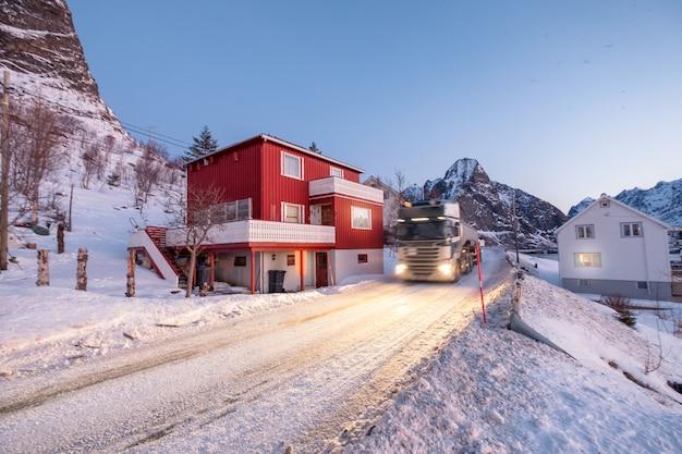 Trasporti il carico su autocarro sulla strada nevosa in valle