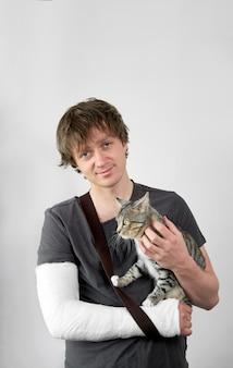 Trattamento conservativo della frattura del braccio. giovane uomo stanco attraente con calco in gesso sulla sua mano in posa con il suo bel gatto