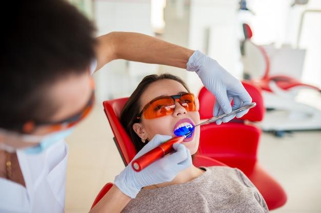 Trattamento di luce sigillo bella ragazza in odontoiatria.